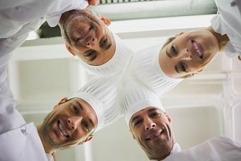 Chefs in toques standing in a circle