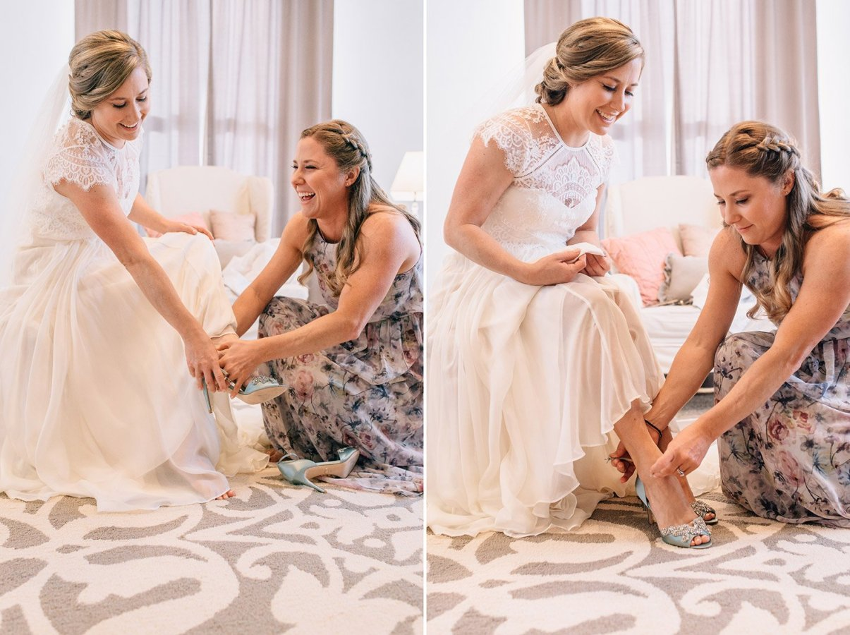 sister helps bride put on her shoes