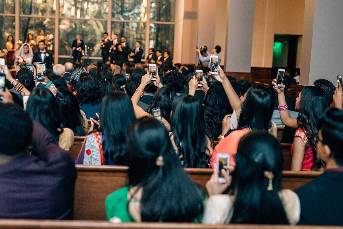 congregation with phones during wedding