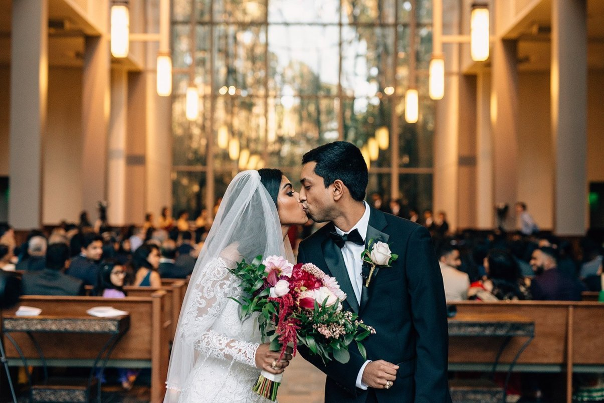 bride and groom kiss during recessional at chapel in the woods
