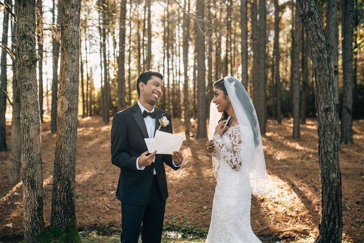 bride and groom laughing while reading letters during first look