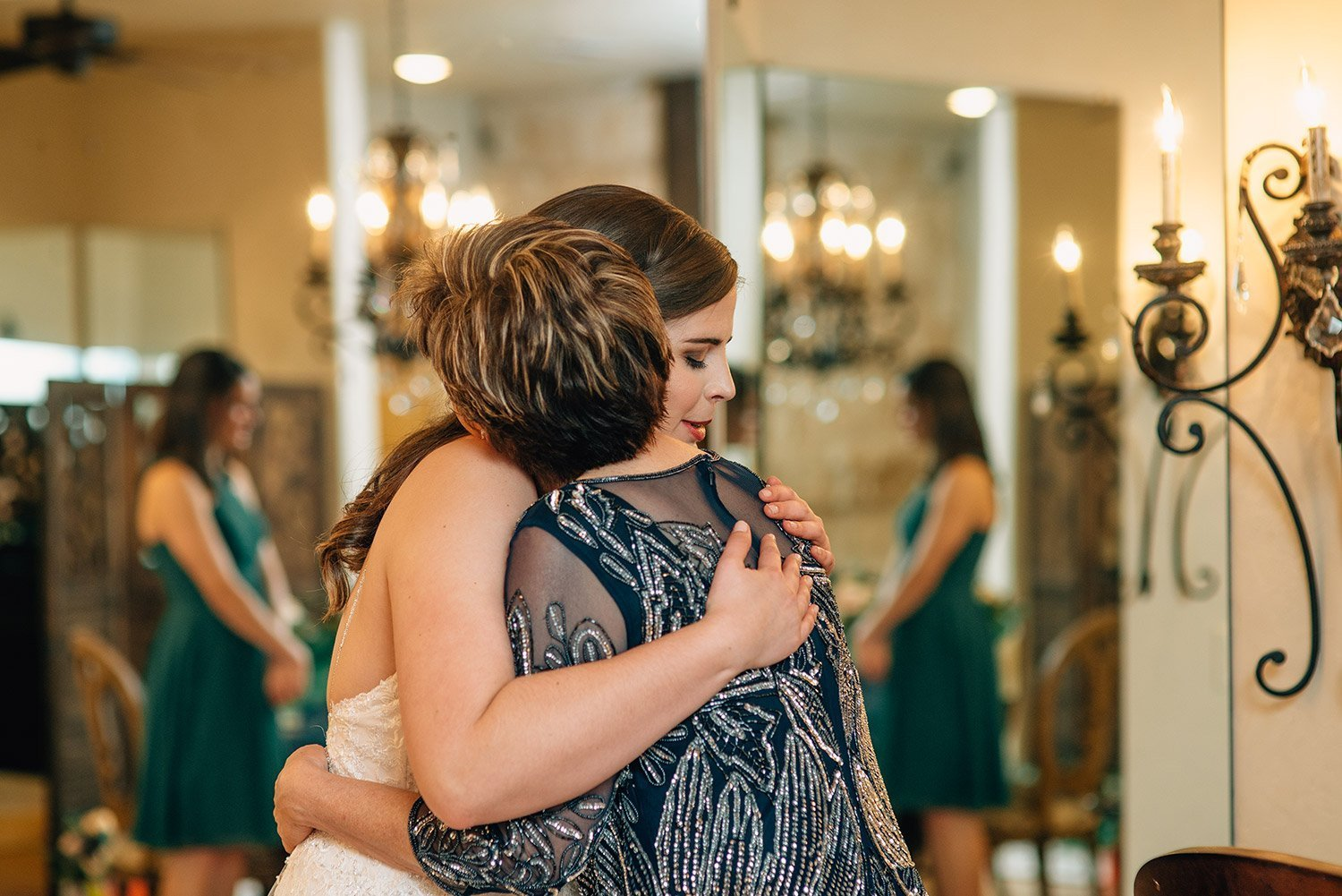 mother of the bride hugs bride in bridal room at the springs event center