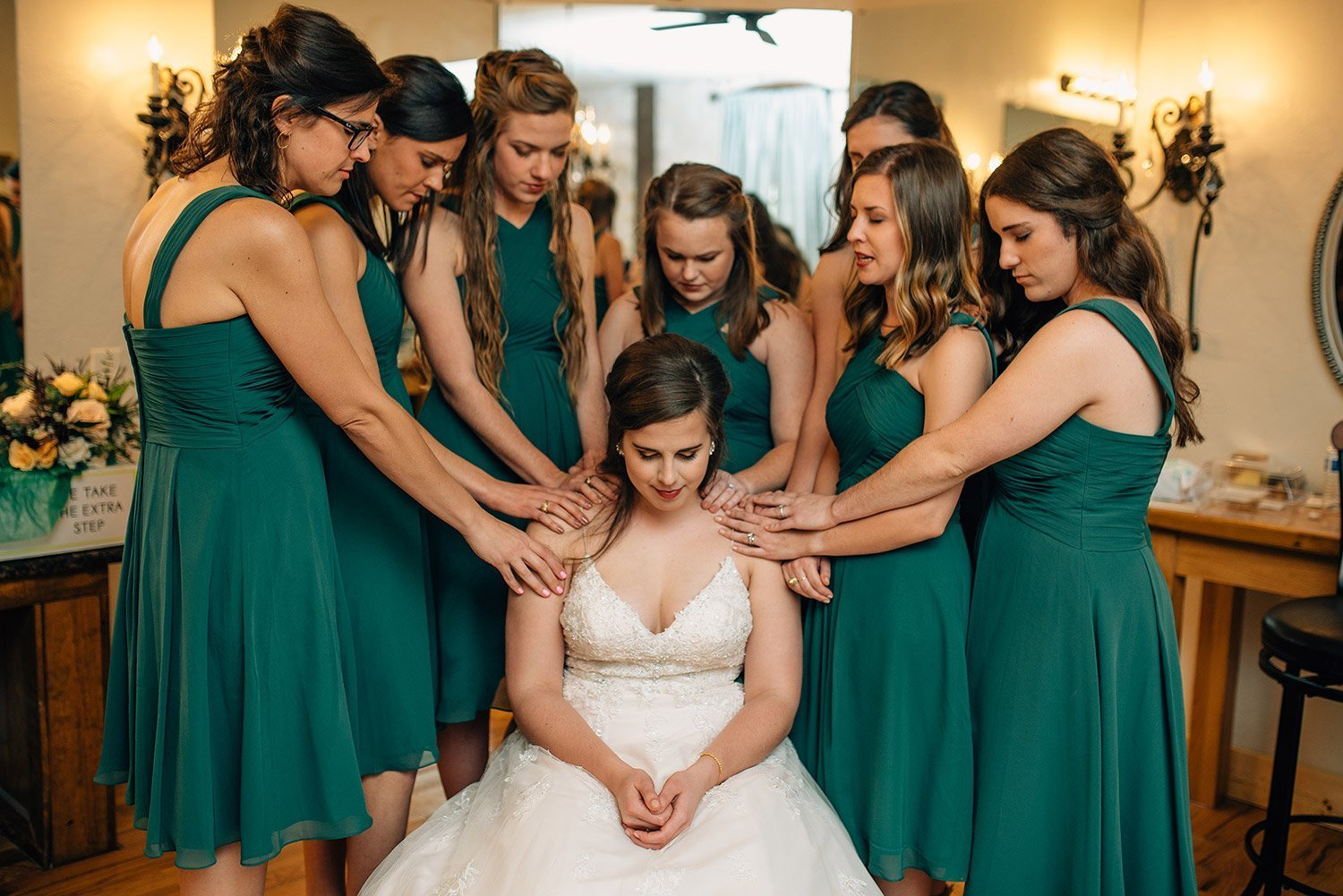 bridesmaids praying for bride in bridal room before wedding at the springs event center