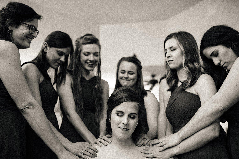 bridesmaids praying for bride before her wedding