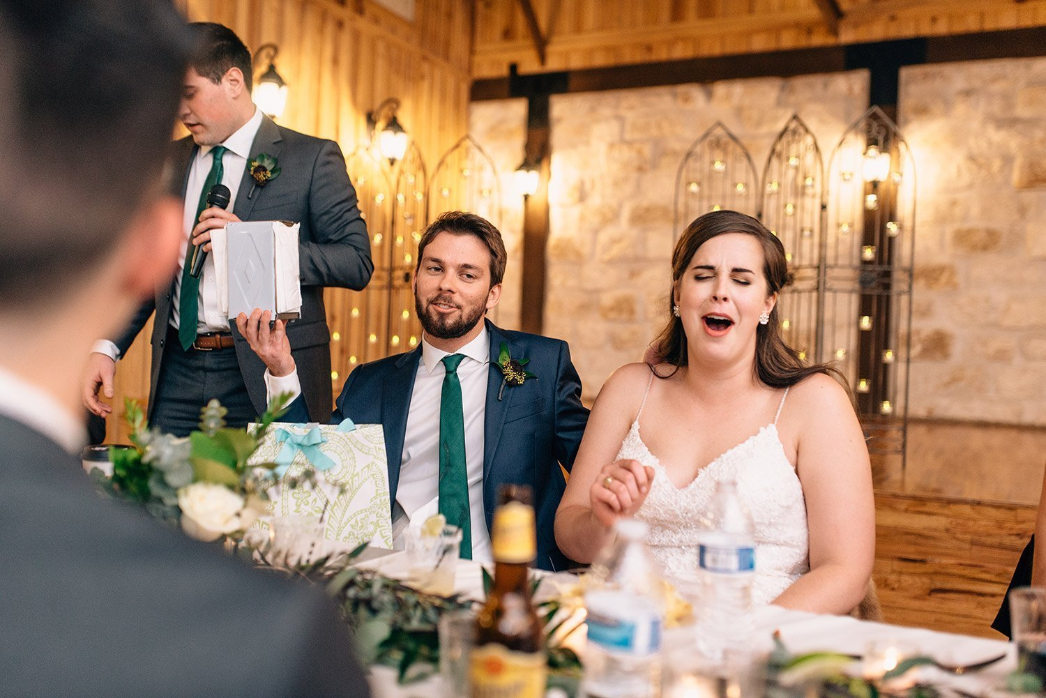bride and groom laugh while best man gives a toast