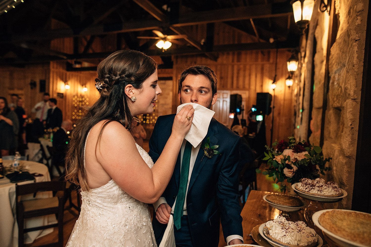 bride wiping grooms mouth after cutting pie instead of cake