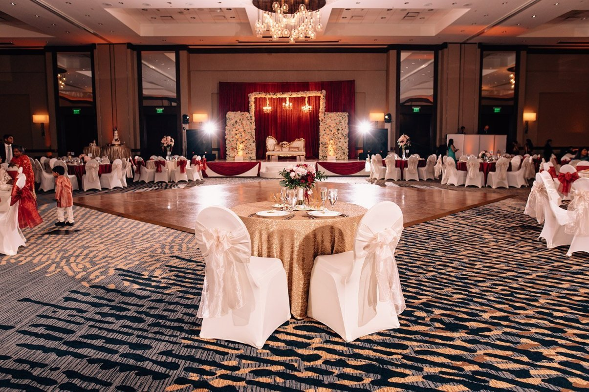 wedding reception at the woodlands resort with white chair covers and red details