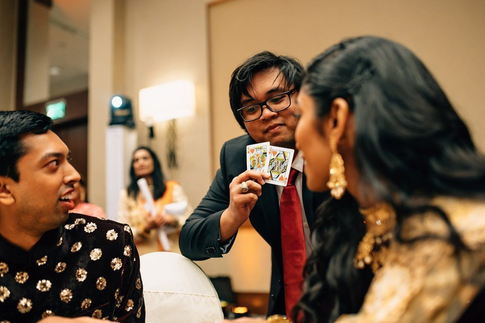 groomsman performing magic trick for bride and groom
