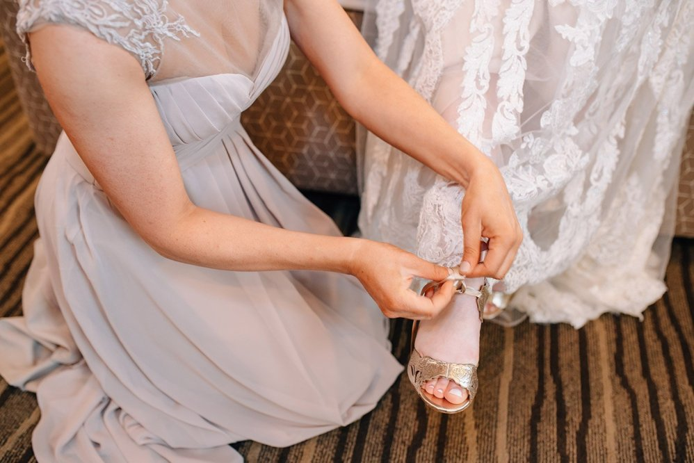 bride's sister helps fasten her harriet wilde shoes