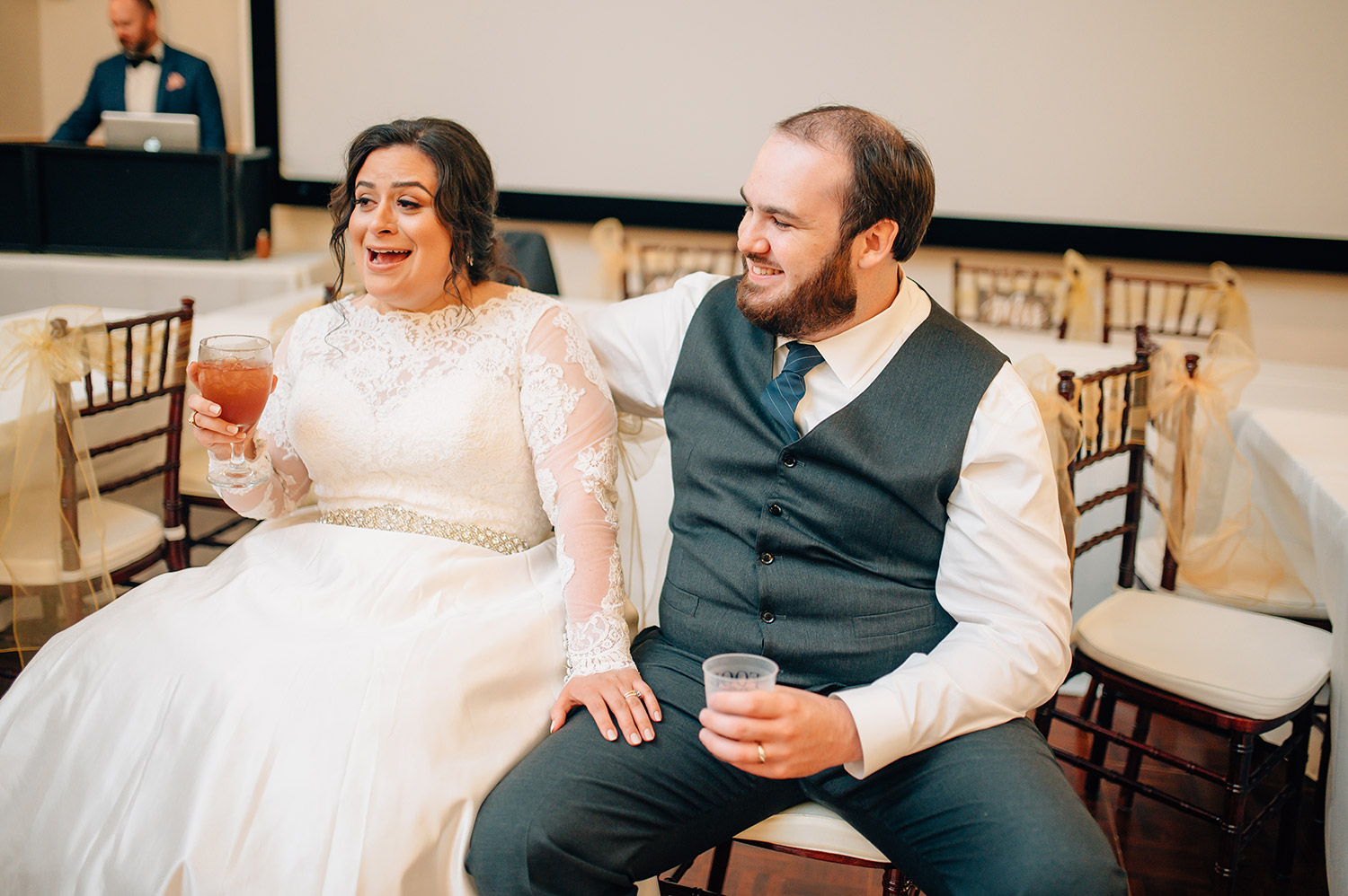bride and groom react to toasts at their wedding reception