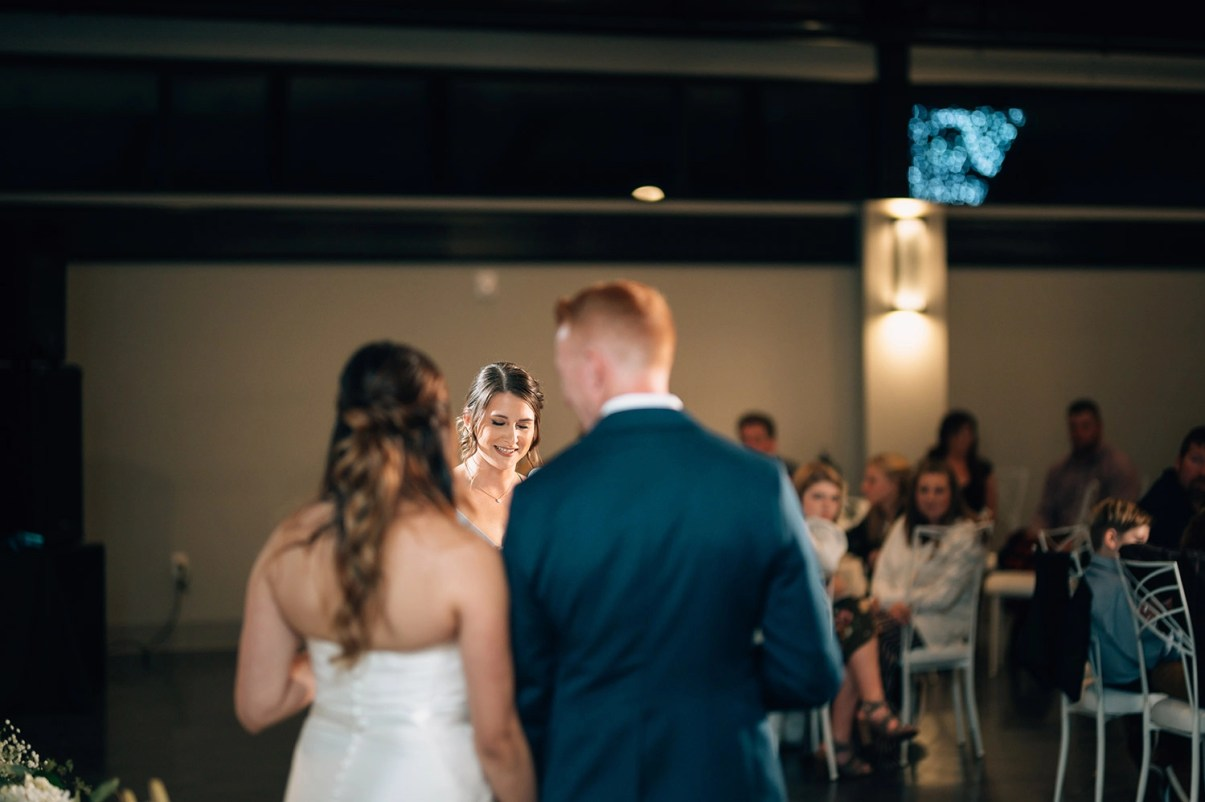 bride and groom listen to bridesmaid give a toast