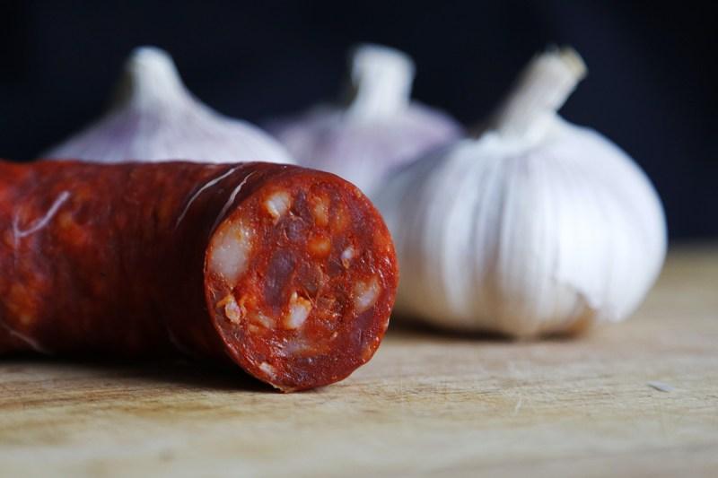 A salami sausage next to some garlic