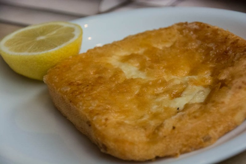 Saganaki, a traditional Greek food of sheep or goat's millk cheese served heated, with a wedge of lemon.