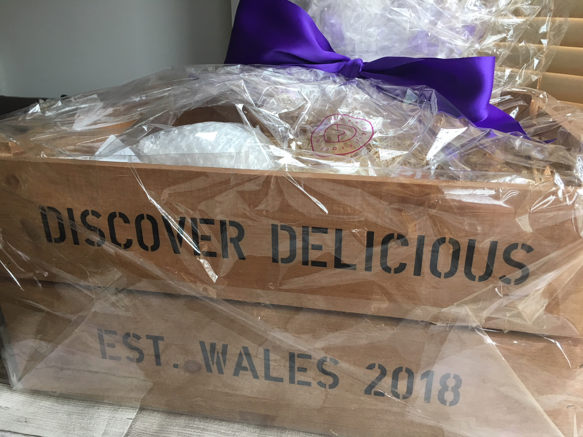 A wrapped hamper from Discover Delicious Wales - a wooden crate wrapped in cellophane and tied with a purple ribbon bow