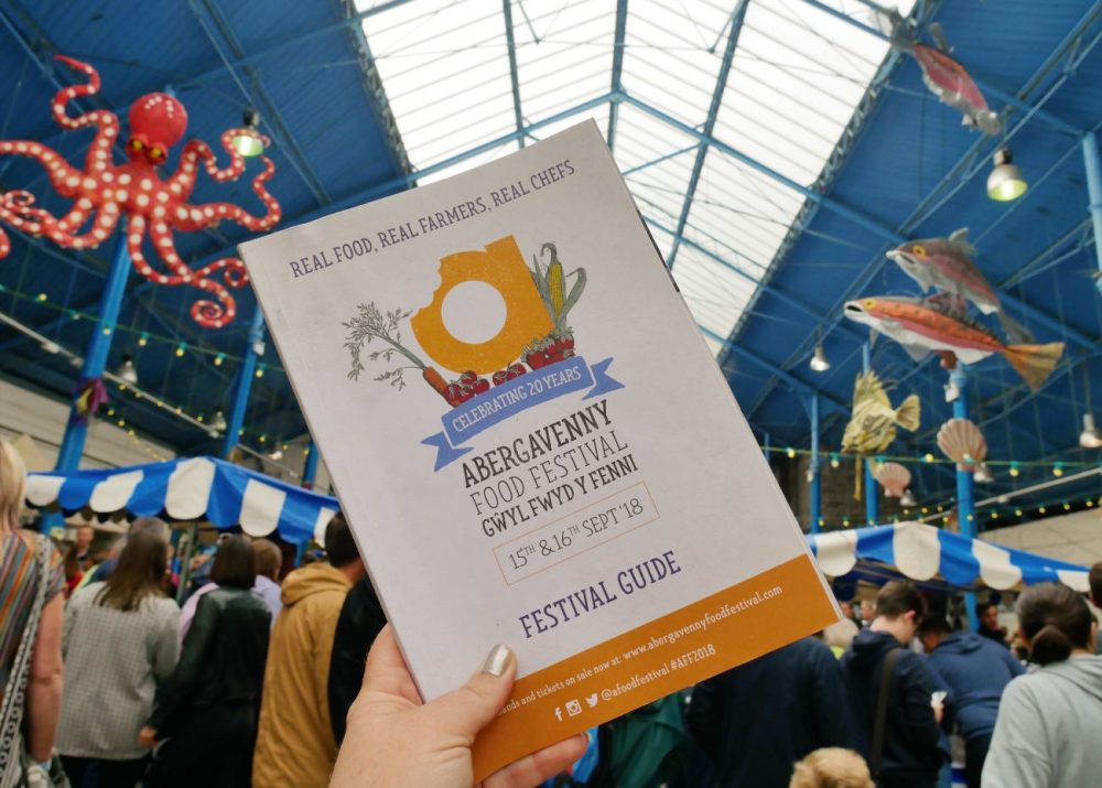 The Official Guide to Abergavenny Food Festival 2018, pictured against the backdrop of the Market Hall.