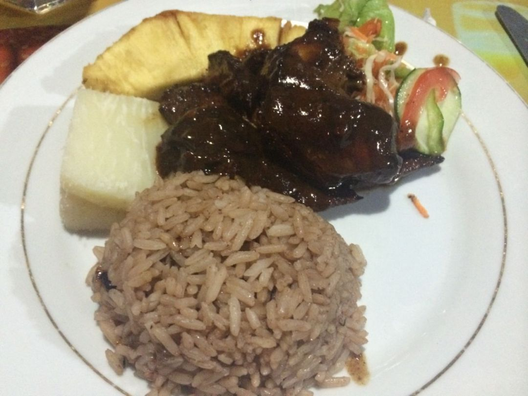 A plate of brown stew chicken with rice and peas, plantain, yam and salad