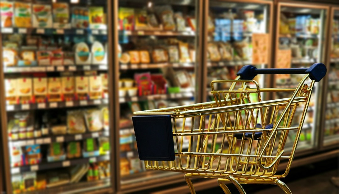 An empty trolley in a supermarket aisle - using supermarket reward cards is a great way to save money for travel