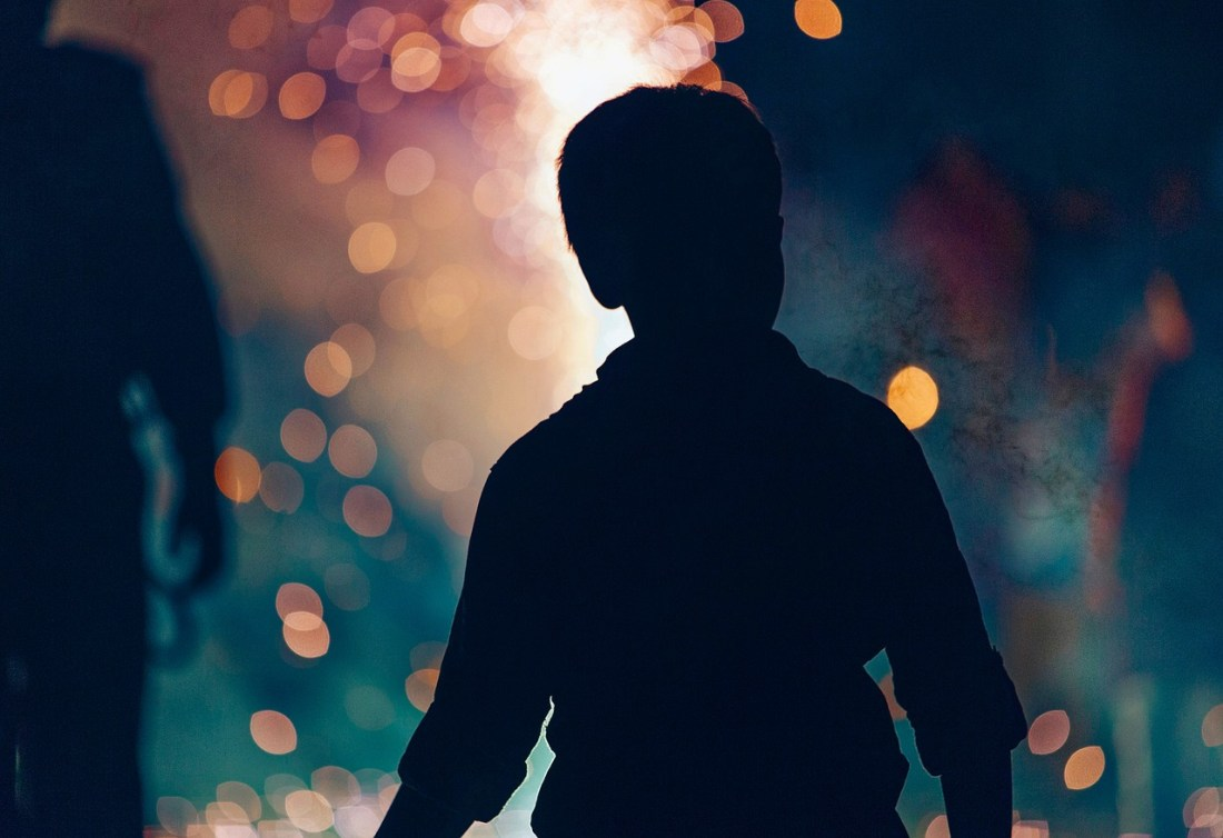 Boy silhouetted watching fireworks on Bonfire Night