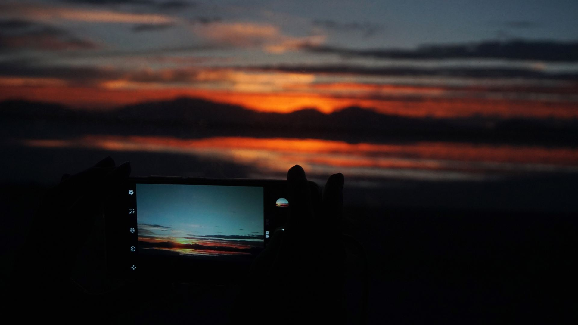 silhouette photography of person capturing sunset with smartphone