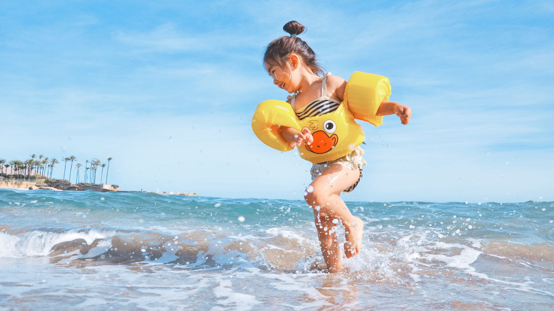 a child runs out of the sea with a yellow rubber duck swim float