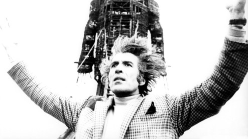 Christopher Lee stands with his arms raised with the WIckerman behind him.