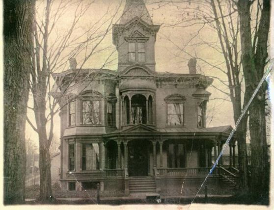 An old picture of a creepy house with a single tower