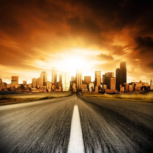 A road leads to a city where the sun, or maybe an explosion, dominates the skyline