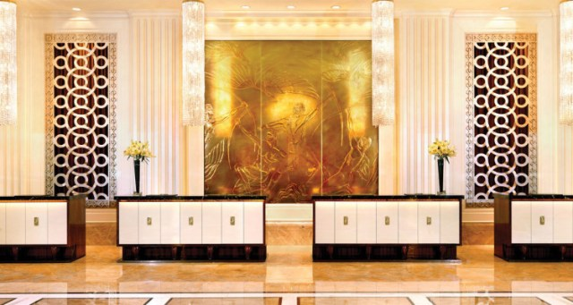 A golden hotel lobby with a huge golden mural on the wall