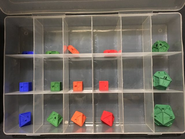 a plastic container with 2x3 in squares, each holding a braille dice in either blue, green, orange, or red. The dice are 4d4, 4d6, 4d8, 1d10, 1d12, and 1d20
