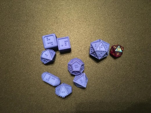A set of blue braille polyhedral dice with a chessex d20 for comparison. The DotsRPG dice have a dotted line at the bottom of several of the sides of dice to show orientation.