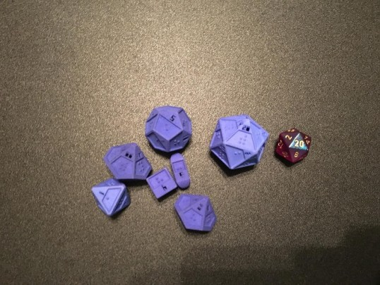 A set of braille polyhedral dice with a chessex d20 for size comparison. These dice show a number cut out on each side, as well as the braille in a depression.