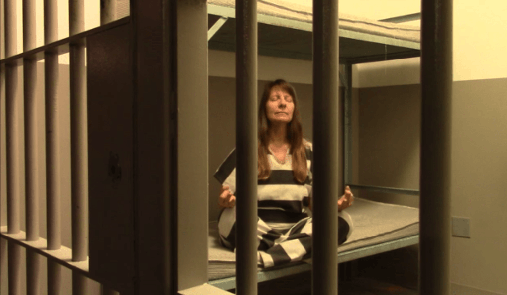 Theresa in Meditation Pose in mock Jail Cell