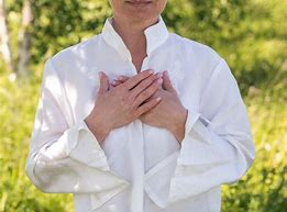 Woman with hands over heart. Heart Connection Pose