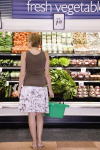 Woman in grocery store produce aisle with shopping basket