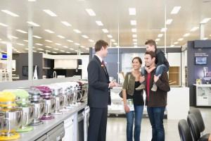 Salesman talking to Hispanic family in appliance department