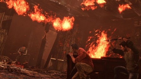 Sully and the player crouch behind cover in a gunfight inside a burning chateau