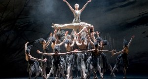 A ballerina is held aloft atop a pyramid of dancers
