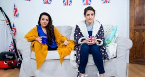 2 girls sat on a sofa with union jack bunting behind them