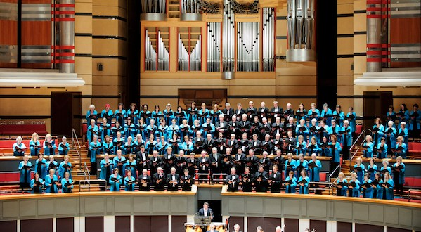 A Gowned choir in front of a grand organ