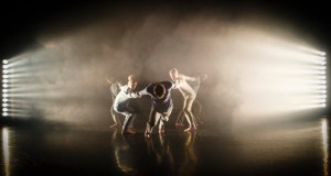 A group of dancers silhouetted through smoke