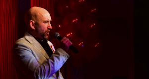 Bald man singing into microphone