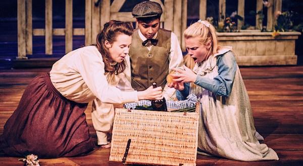 Three children sit around a basket
