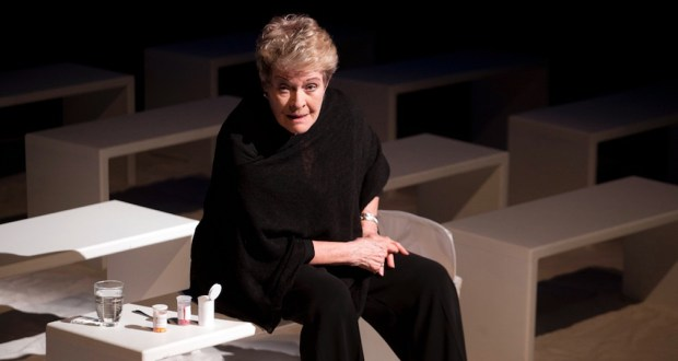 Janet Suzman as Rose sits on a white stool