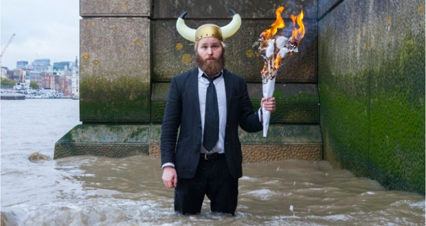 man in viking helmet standing in river with torch