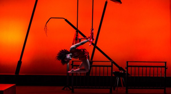 A dancer hangs in front of a red background