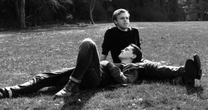 Two men lying together in a park