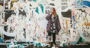 woman smoking stands in front of a wall of torn posters
