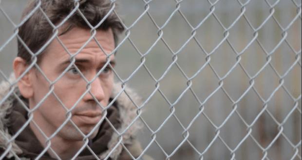 man behind wire fence