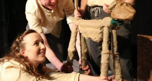 Three people operating a puppet dog