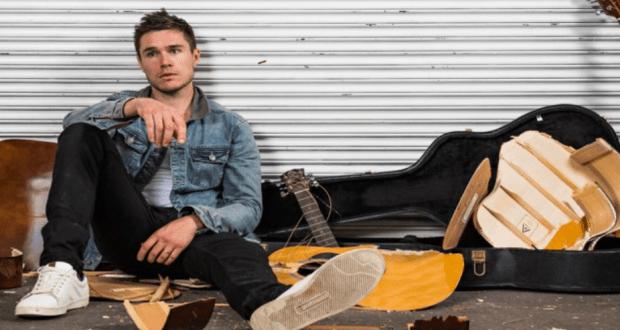 man sitting on floor sam underwood with guitar beside him